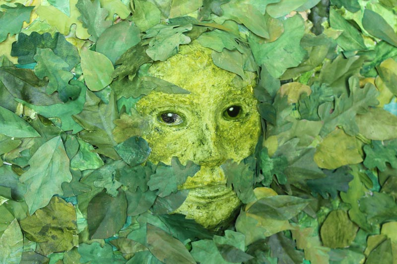 Mixed media painting of the Green Woman, face amongst the leaves at kathycassell.com